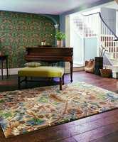 Tapet, teppe og pute i fred og fordragelighet, i samme fargepalett og med flere mønster mot hverandre.