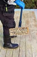 <b>GREI SKURING:</b> Hold overflaten fuktig i cirka et kvarters tid, og skrubb deretter treverket godt med en stiv kost som dyppes i kaldt vann.