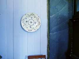 Mur og treverk i forskjellige blåfarger. På muren er det også benyttet gammel maleteknikk. Porselentallerkenen fra slutten av 1800-tallet er malt med koboltblå farge og brent ved 1.200 grader, det eneste fargeprodukt som tåler en slik varme.