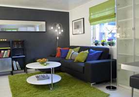 Den sorte veggen i stuen gir ro, mens grønnfargen gir et frisk preg. Speil i vindusnisjen slipper ekstra lys inn.