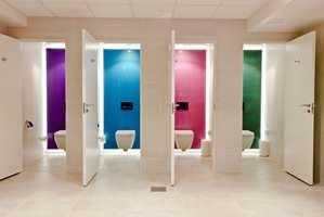 Bak det vegghengte vannklosettet er hvert avlukke dekorert med en akrylplate i en egen farge. Bevegelsesmarkøren på den berøringsfrie betjeningsplaten lyser med LED-lys i samme farge som veggen.