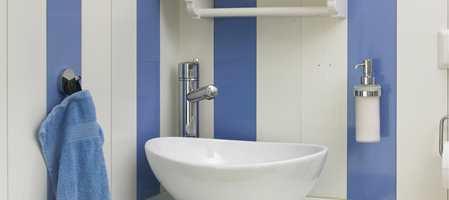 Også små rom kan gjøres fremtredende. Se bare på dette gjestetoalettet, som har fått halvblanke, blå striper mot den matte hvite veggen.