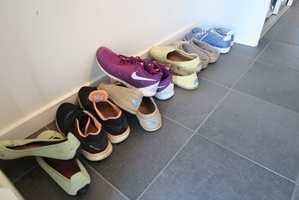 Noen sko ligger og slenger på gulvet. Andre har sitt eget stativ. En gummi- eller teppeflis på veggen sørger for at skoene ikke skitner til.