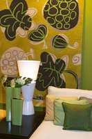 Grønne varianter i puter og teppe. Her supplert med en vase i lyst blått. En kombinasjon vi ofte finner igjen i denne stilen.