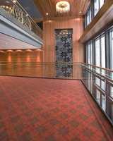 Stilige fargesammensettninger med beiset panel og bjelker, samt tepper med rødlig bunnfarge og gråbrunt mønster. Utsmykningen på veggen er strikketekstil fra Dale of Norway med et velkjent mønster.