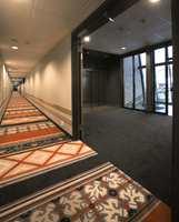 Teppebelagte korridorer hvor interiørarkitekt har valgt en modifisert variant av ege-mønsteret Village Print. I områdene foran heisene er det mest praktisk med et ensfarget grått teppe.