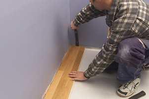 Skyv bordet på plass med en baksmelle eller et brekkjern som her. Bruk helst baksmelle hvis du har liten trening, brekkjern kan ødelegge veggen.
