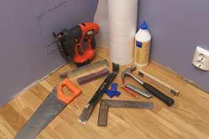 Verktøyet til parkettlegging: Skumplastduk, lim, parkett, baksmelle, brekkjern, slagkloss, brekkjern, kiler, blyant, kniv, hammer, tommestokk, håndsag og vinkeljern.
