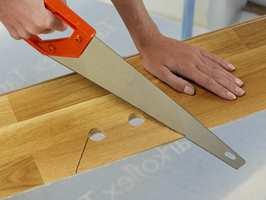 Hvis bordets langside støter på et rør, borer du et hull som er ca 16 - 20 mm større enn diameteren til røret. Marker med en blyant der du skal sage. Sag av den biten som skal plasseres bak røret, nærmest veggen. Sag slik bildet viser.
