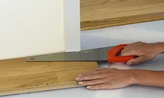 Dørkarmer kan tas av og flyttes, men det er som regel enklest å sage dem av. Bruk et løst gulvbord som mal for høyden, og sag av karmen med en fintakket sag. Legg gulvet inn under karmen. Pass på at gulvet ikke blir klemt mellom undergulvet og karmen.