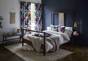 <b>FARGESPILL:</b> Kontrasten mellom hvitt og mørk blå mykes opp med gardiner i blomstermønster og flere farger. Tekstil fra Scion/Tapethuset.
