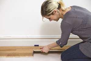Trykk ned kiler mellom gulvet og veggen for å lage en bevegelsesfuge på cirka 10 mm.