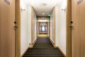 Teppene i korridoren baserer seg på to hovedfarger, røde og grønne fargevariasjoner, med hjelp av en mørk antrasitt bakgrunn. De fargede stripene i teppene skaper endring i intensitet og distanse.