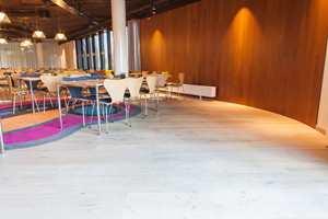 Frokostsalens lyse tregulv og mørke veggpaneler mykes opp med avrundede innredningsdetaljer og fargerike tepper.