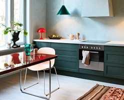 07. Kjøkkenet har en lettere, lysere atmosfære, med nyanser i blått og grønt. Røde aksentfarger skaper forbindelse med den tilstøtende spisestuen.