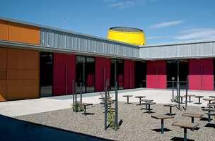 Skolegården - et fargerikt atrium der 'pipene' fra auditoriene stikker opp over takflatene.