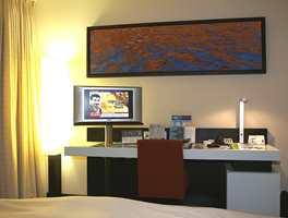 Et standard hotellrom med LCD flatscreen, kaffe- og temaskin, buksepress, high-speed internet-tilgang og bollelignende servant på badet.