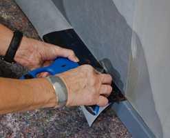 <b>STÅLSPARKELEN:</b> legges ned mot listen og presses helt inn til veggen, mens kniven føres langs sparkelbladet og helt ut. (Foto: Chera Westman/ifi.no)