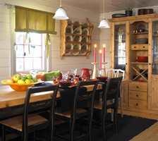 Tre meter spisebord i lysnede omgivelser – her kan man sitte lenge og vel i hyggelig lag.