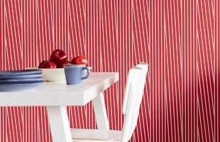 <b>LEKENT:</b> Røde og hvite tynne striper på veggen skaper et lekent uttrykk på kjøkkenet. Tapetet som er satt opp her er fra kolleksjonen Stripes fra Storeys. (Foto: Storeys)