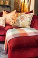 <b>LUNT:</b> Nå vil mange ha det lunt og hyggelig i stua. Med varme rød- og oransjetoner, myke tekstiler og taktile materialer kan den drømmen gå i oppfyllelse. Her er det brukt tekstiler og møbler fra Green Apple. (Foto: Chera Westman/ifi.no)