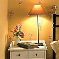 Veggen bak sengen fungerer som kontrastvegg med sitt storblomstrete mønster.