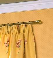 Småmønstret tapet oppleves rolig nesten ensfarget mot det store mønsteret på gardin og endevegg.