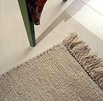 En vevet rye i lys ull på det hvitmalte gulvet er innbydende for nakne føtter.