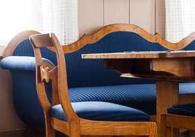 <b>BLÅ SOFA:</b> Valget av tekstiler følger den nøkterne stilen i huset. Fargen refererer til det historiske, mer enn å kopiere.