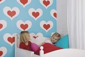 Jentene koser seg på barnerommet med blå og røde hjerter. Tapet fra barnekolleksjonen «Kompis» til Inspirasjon Interiør.