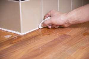 Bruk en gumminal som her eller fingeren. Slike gumminaler fås hos rørleggerforhandlere og noen flisbutikker.