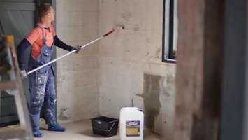 <b>BINDER STØV:</b> Halvor Bakke er også praktisk handyman, og med rull på langt skaft sparer han ryggen når støvbindingen påføres.