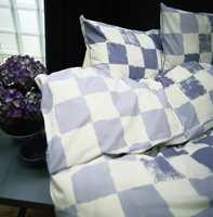 Sengetøy i glatt, satenglignende bomull med store og ujevne ruter i to nyanser av blått. Mønsteret finnes også i andre farger.