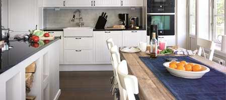 Kjøkkenet er blitt favorittplassen i sommerhuset. Ved det tre meter lange kjøkkenbordet kan barna lese eller male en regnværsdag, samtidig som det er plass til å dekke på bordet.