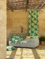 Med puter og gardiner med tropisk mønster kan vi holde lenge på eksotiske ferieminner eller sommerfølelse. Her er Manila Fabric fra Sanderson som føres av INTAG.