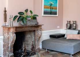 <b>SÆRPREG:</b> Hjemmets særpreg og karakter fremheves av fargene, som her i stua, der den duse, lune rosafargen får den gamle ovnen til å skinne. Veggene er malt med Licetto i fargen Skin Powder.