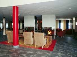 Hotellet ønsker deg velkommen med lune flammer fra gasspeisene. Glassvegger gjør at de synes like godt fra bar og salong som fra resepsjonsområdet.