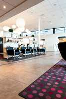 Lobbyen er utstyrt med flere sittegrupper og lunende tepper på gulvet som også har en gunstig innvirkning på akustikken.
