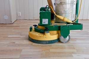 For å lysne et mørknet gulv må all gammel lakk fjernes med gulvslipemaskin.