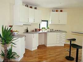 Et delvis sirkelformet kjøkken på grunn av siloformen. Den originale grove siloveggen er beholdt og er kun malt.