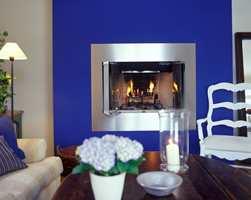 Peisen har ramme i børstet stål, og den blå veggen er malt med matt maling i kraftig blått.