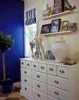 En hvitmalt kjøpmannsdisk med mange skuffer er også et nødvendig møbel i en entre.