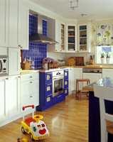 Kjøkkenet med eggeskallhvit innredning kler blå detaljer.