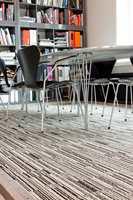 Teppegulvet i møterom og ved kontorpultene er fra Modulyss og kolleksjonen White&Black, og fargen Black&001 i brede striper.