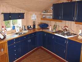 Kjøkkenet før – mye mørkere, både innredning og vegger.