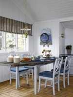 Veggene er lyse, understellet på spisebordet er malt i en gråfarge, stolene likeså. Den nye bordplaten er laget av drivved. Gardinen tilfører rommet tekstur og en lett tyngde.
