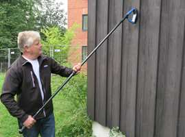 Maling og løse rester må skrapes av husveggen før den kan males.