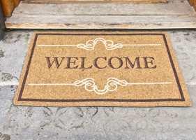Hold smusset ute med en dørmatte, og hils samtidig gjestene velkommen med et dekorativt teppe på gulvet.