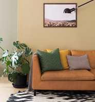 <b>DYBDE:</b> I et rom malt i varme farger gir små innslag av sort rommet dybde og strammer opp helheten. Veggene bak sofaen er malt med Butinox Interiør Stue & Sov Matt farge 5939 Dijon.