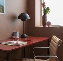 <b>SORT LAMPE:</b> Den sorte lampen er ikke tilfeldig valgt eller plassert. Den er den lille kontrasten som får rødtonene til å leve litt ekstra. Veggen er malt i Butinox farge 5926 Frappe, og skrivebordet med Quick Bengalakk farge 5933 Årgang.